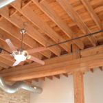 Ceiling detail. Post and beam, ceiling fan, track lighting.