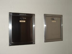 Garbage and recyclable common chute receptacles on a condo floor.