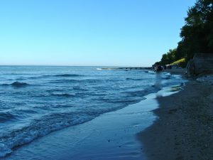 A Lake Michigan beach with a groin, in the distance, and extending away from shore to limit erosion of beach sand from erosion of wave action.
